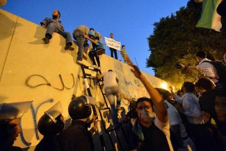 Egyptian police stood guard as protesters climbed down a wall outside the US Embassy in Cairo Tuesday.