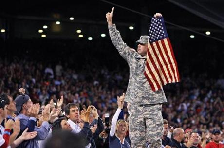 Command Sergeant Major Brian Branley of Medford lifted an American flag atop the Red Sox dugout between innings during the 9/11 anniversary remembrances at Fenway Park.