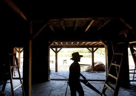Jacob Flaud, from a Newburg, Pa., timber structures company, was ready to cut wooden pegs during construction of a new barn at Hornstra Farms in Norwell.