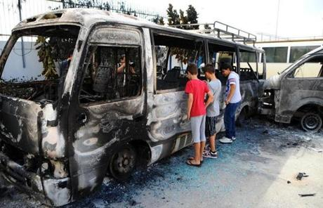 Children looked at a burned out bus near the US embassy in Tunis a day after protesters stormed the compound.