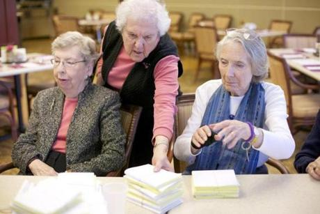 Elaine Rothman, 85, reached between Mary Lou Touart, 89, (left) and Agnes Burke, 84, to collect pro-Obama postcards.  Both President Obama and Mitt Romney are getting help from older supporters as they compete for the senior-citizen vote on Nov. 6.