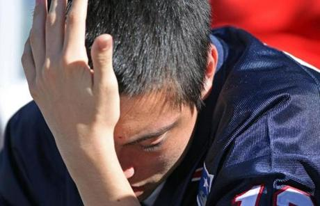 A despondent Patriots fan was pictured with his head in his hand after Arizona scored a touchdown in the fourth quarter.