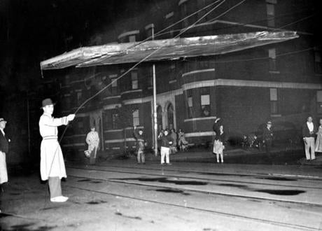 September 23, 1938: After the hurricane, John Runane of Roxbury holds tightly to a wire below the roof of a house suspended by trolley wires. ( Note the attempt to add features to his face and jacket by painting on the photograph. This retouching was done often to prints in the production process in newspapers decades ago. This is a past practice that no longer exists.)