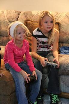 Megan Nighbor (left), 12, who has progeria, played a video game with her cousin Taylor Stellmacher in Wisconsin.