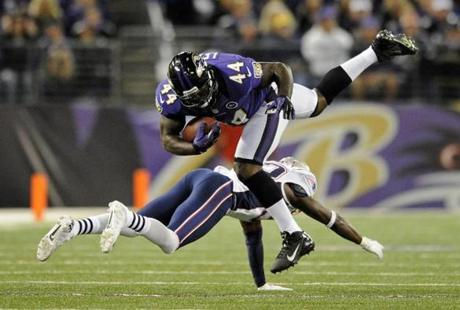 Ravens fullback Vonta Leach (top) is upended by Patriots cornerback Devin McCourty as he rushes the ball in the first half.