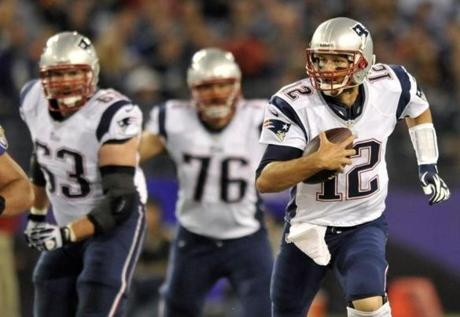 Patriots quarterback Tom Brady (right) rushed the ball past teammates Dan Connolly  (rear left) and Sebastian Vollmer in the first half.