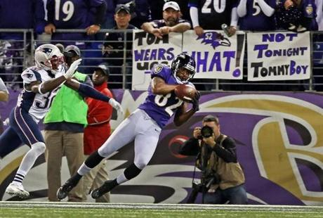 Torrey Smith  hauls in a fourth quarter touchdown pass from Joe Flacco as the Patriots' Devin McCourty defends.