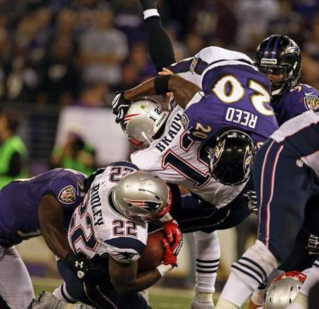 Patriots running back Stevan Ridley is taken down on a third down running play, as the Ravens' Ed Reed sails over quarterback Tom Brady as he tries to get in on the tackle.