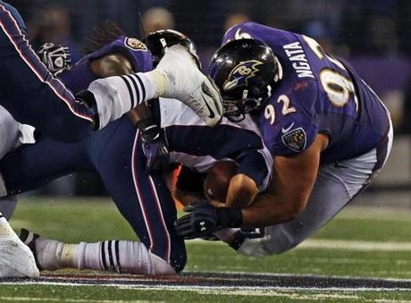 Patriots quarterback Tom Brady is sacked by the Ravens Dannell Ellerbe (left) and Haloti Ngata (right) on a second downplay during the last New England possession of the game.