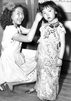 January 27 1946 / fromthearchive / Globe file photo / Boston school children from the Quincy school on Tyler Street, under the supervison of headmaster John P. Maloney, are rehearsing for a celebration of the Chinese New Year. Pauline Yee ties a hair bow and puts the finishing touches on the holiday costume for Caroline Jane Wong