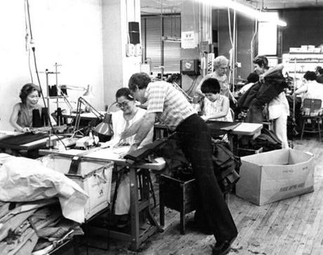 July 13 1981 / fromthearchive / Globe staff photo by Paul Connell / Jose Rivera, the owner of a small apparel factory that employed 35 people at 15 Kneeland Street helps a seamstress with her work. Harrison and Kneeland streets were once the center of the apparel making industry in New England.