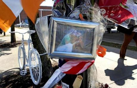 "On West Broadway, mourners have left a ""ghost bike,"" flowers, Irish flags, and handwritten notes for Tanya Connolly."