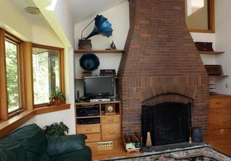 A brick fireplace modeled after one in the Isabella Stewart Gardner Museum stretches from floor to ceiling.