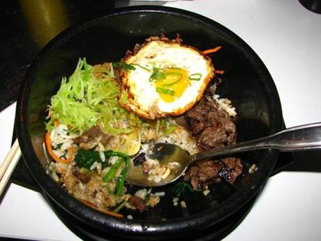 Bibimbap is rice topped with vegetables, meat, and egg in a hot stone pot.