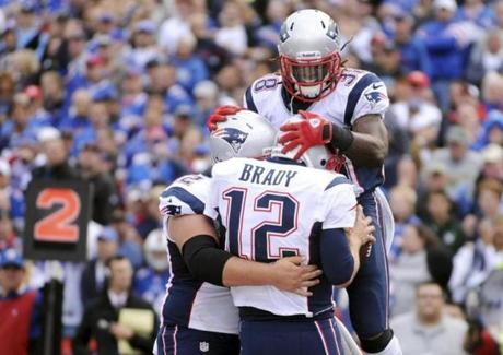 Patriots offensive lineman Ryan Wendell (left), Tom Brady, and running back Brandon Bolden celebrated the quarterback's touchdown.