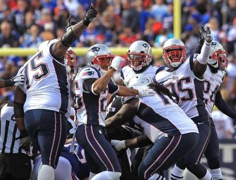 The Patriots defense celebrated after forcing a fumble by Bills running back Fred Jackson.