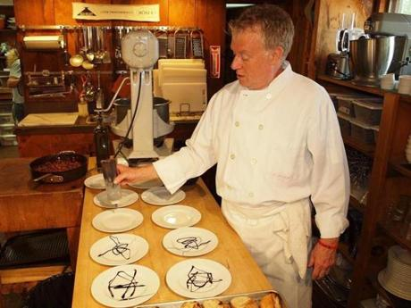 At The Silo Cooking School in New Milford, Conn., chef Bill Cosgrove demonstrates a technique of plating, drizzling balsamic vinegar on plates for his cooking class.