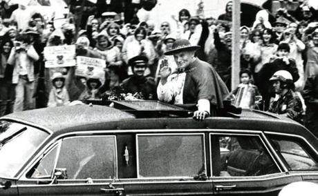 October 1, 1979 : Pope John Paul II passes along people lined up on Boylston Street in a black limousine with a sunroof, through which he stood for his welcoming procession through the city. Wearing a red hat as protection against the sporadic rainfall, the Pope smiled broadly and waved continuously at the thousands lining the streets.