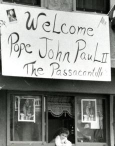October 1, 1979: Two-year-old Maria Renda looks out a window below a banner from the Passacantilli family welcoming Pope John Paul II to the North End.