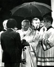 October 1,1979: Pope John Paul II administers communion during the rain's heaviest downfall. Several hundred priests were dispatched into the crowd to distribute communion. The paper-thin hosts, wafers of unleavened bread were in danger of being melted by the pouring rain. People voluntarily held their umbrellas over the priests to protect the chalices filled with the communion bread as the Pope is shown shielded here.