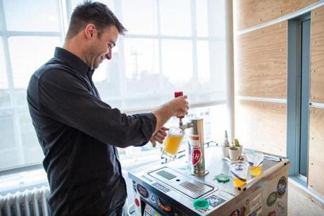 Senior digital artist Seth Borne pours himself a beer from the tapped