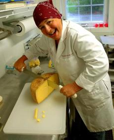 ROBINSON FARM: Pam Robinson cut into a wheel of aged cheese at her Hardwick farm. She and her husband, Ray, sell grass-fed beef, too.