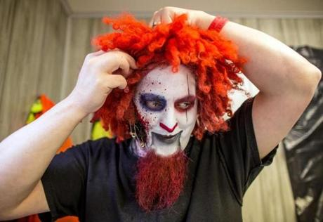 A clown put on his red wig.