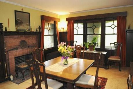 The dining room features intricate window designs and a brick fireplace
