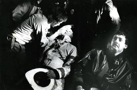 October 14 1973 /  John White, District Fire Chief of Boston gets his eye treated as other firefighters line up for aid. Over 2000 firefighters from 85 communities converged on Chelsea to battle the fire.