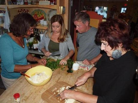 At a cooking class at the Roman Table, Lorraine Schinelli (left) mixes up manicotti filling with students.