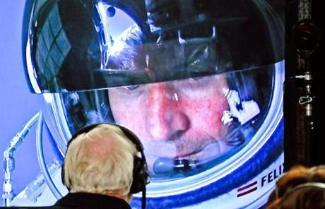 Felix Baumgartner is seen in his capsule on a screen at mission control during his ascent.