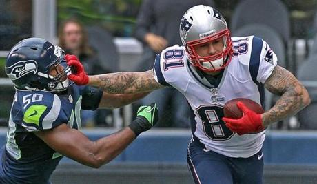 Patriots tight end Aaron Hernandez caught a pass from Tom Brady and stiff armed Seatle linebacker K.J. Wright as he picked up some yardage after the catch.