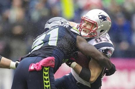 Wes Welker of the New England Patriots is hit by Jeron Johnson of the Seattle Seahawks after a reception.
