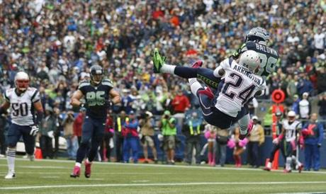 Seattle Seahawk Doug Baldwin caught a touchdown as New England Patriots cornerback Kyle Arrington  tried to defend the pass in the first half.