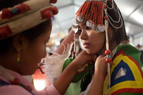 Tenzin Kalsang, 17, helped Tenzin Choedon, 13, with her traditional dance costume before their performance.