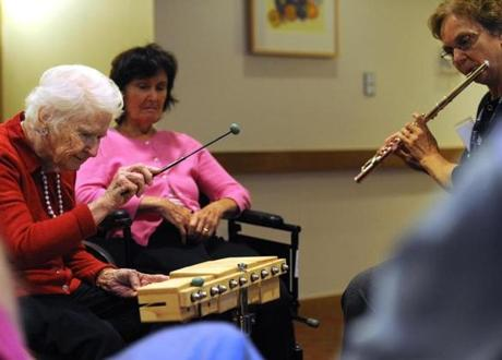 In the music class at NewBridge on the Charles, Dorothy plays percussion and therapist Sally Harrison plays the flute.