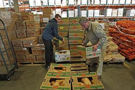 Boston, MA., 10/17/12, Scott Helman chronicles the Greater Boston Food Bank. Volunteer Jack Doherty, left, and Ed Coye of the Bourne Food Pantry. cq, in the Yawkey Distribution Center. Section: Magazine Suzanne Kreiter/Globe staff