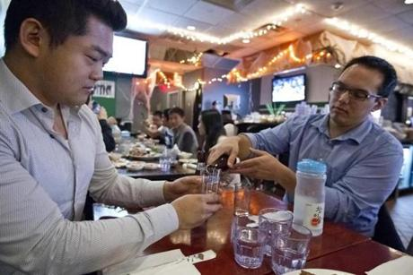 Richard Kim (left) observed the Korean tradition of having someone else pour your drink, with Andrew Hubbard.