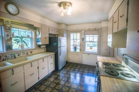 A view of the kitchen, which has older appliances and linoleum floors.