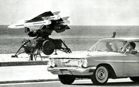 October 27, 1962 / US Army anti-aircraft rockets were mounted on launchers and pointed out over the Florida Straits in full view of the public at Key West, Florida. These rockets in position on a formerly public beach are viewed from automobiles driving along Roosevelt Boulevard. The rocket positions are manned day and night. Off-duty missilemen sleep in sleeping bags on the beach while other soldiers walk guard duty with rifles.