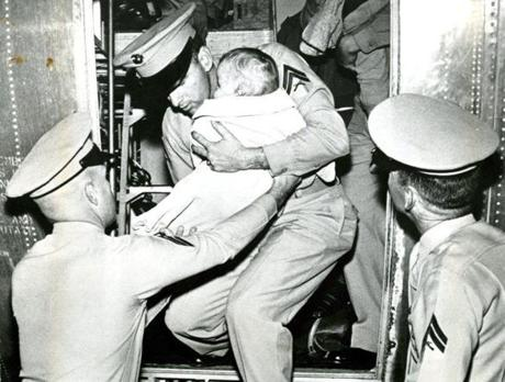 October 22 1962 / An unidentified baby, one of several hundred dependents of US Navy personnel evacuated by air from the US Naval Base at Guantanamo, Cuba, is removed gently by Marines from the troop transport that brought him home.