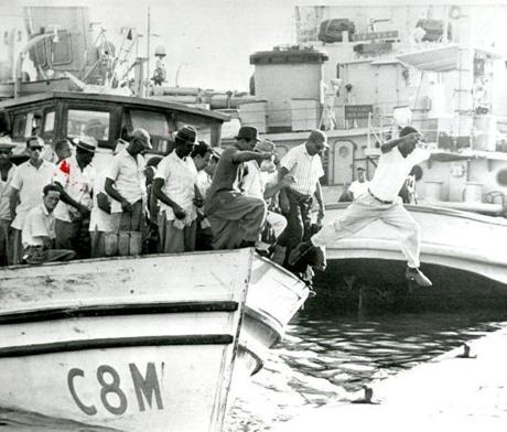 September 19 1962 / A Cuban worker leaps ashore from a ferry boat that brings the regular morning force of workers to Guantanamo Bay Naval Base. Each morning the ferry hauls Cuban workers from a nearby town to the US base. In the background are US ships. Fidel Castro's militia units have stopped Cuban cars and commercial buses from transporting Cuban workers into the base at Guantanamo. The Navy has been sending its own buses to the base's main gate to pick up the workers.