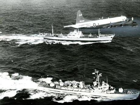 November, 1962 / Soviet missiles were withdrawn from Cuba in November in one climactic chapter of the Cuban crisis. A US Navy patrol plane hovers overhead as the destroyer USS Barry escorts the Soviet freighter Anesov with a presumed cargo of outbound canvas-covered missiles on its deck.