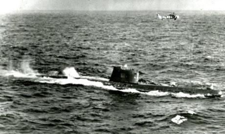 November 9, 1962 / A US Navy helicopter hovers over a Soviet submarine operating tin the area of the Cuban quarantine fleet operations.