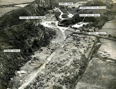 October 26, 1962 / This US aerial reconnaissance photograph of a missile site on Cuban soil was released by the Pentagon and used by US Ambassador Adlai Stevenson at the United Nations. Soviet Ambassador Valerian Zorin charged first the US had no evidence of such missile sites. When the photographs were produced he branded them forgeries without looking at them. Military men adept at interpreting aerial photographs pointed out that at left are the oxidizer vehicles and at right, fueling vehicles. Missiles, unlike automobiles must carry their own air to mix with the fuel. Above the fueling vehicles are two