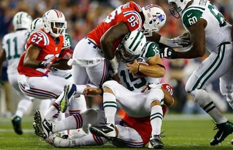 Jets backup quarterback Tim Tebow was tackled by multiple New England defenders.