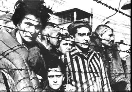 Auschwitz inmates stood behind barbed wire during the 1945 liberation of the Nazi concentration camp in Poland.