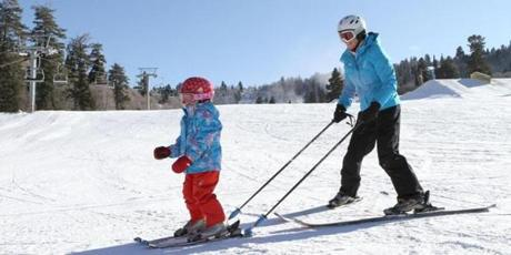 Olympic champion Picabo Street, spokeswoman for Launch Pad, helps a young skier learn to turn and balance using Hookcase