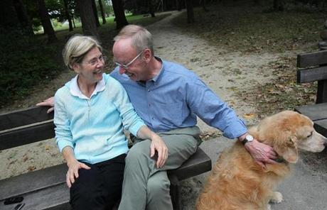 Warren and Mann and their dog Otis at the Fresh Pond Reservoir. Warren and Mann met at a law conference.