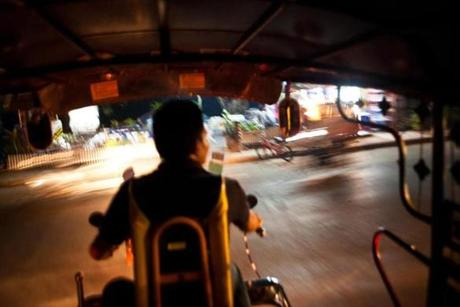 The view from inside a three-wheeled tuk-tuk taxi in Luang Prabang.tuk-tuk taxi in Luang Prabang.